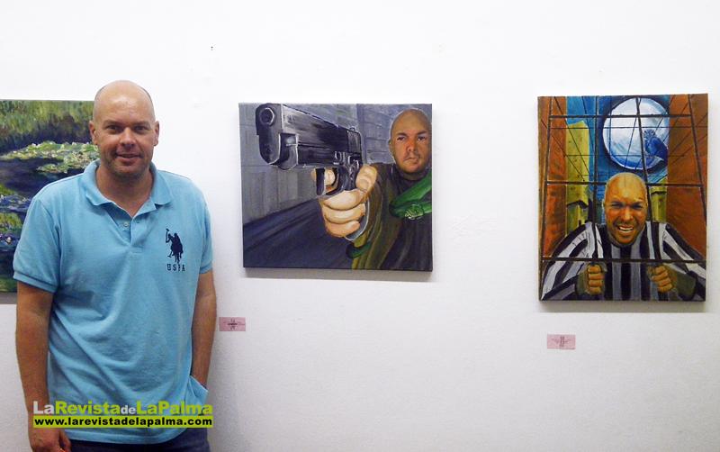 Uno de los alumnos del curso de pintura junto a dos autoretratos